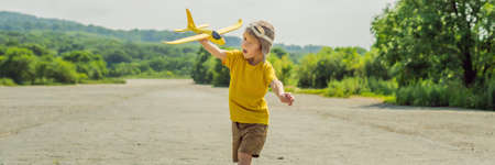 Happy kid playing with toy airplane against old runway background. Traveling with kids concept.