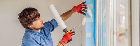 Man in a blue shirt does window installation. BANNER, LONG FORMAT Standard-Bild - 114498706