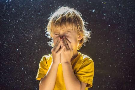 Allergie à la poussière. Le garçon éternue parce qu'il est allergique à la poussière. La poussière vole dans l'air rétroéclairé par la lumière