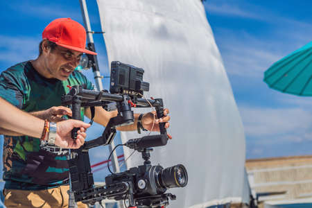 Production team on a commercial video shoot. Steadicam operator uses the 3-axis camera stabilizer and cinema-grade camera Imagens