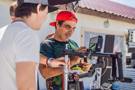 Steadicam operator prepare camera and 3-axis stabilizer-gimbal for a commercial shoot Imagens