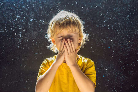 Allergy to dust.Boy sneezes because he is allergic to dust. Dust flies in the air backlit by light. 版權商用圖片