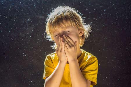 Allergie voor stof. Jongen niest omdat hij allergisch is voor stof. Stof vliegt in de lucht, verlicht door licht Stockfoto