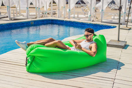 Young man enjoying leisure, lying on the air sofa, near the pool.