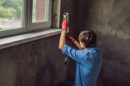 Man in a blue shirt does window installation Standard-Bild - 114999852