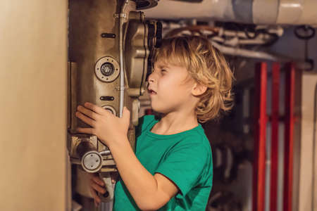 The boy looks through the periscope on the submarine