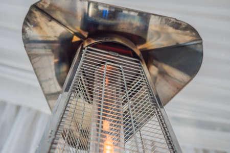 Calentador de lámpara de calefacción colocado entre las mesas de un café abierto