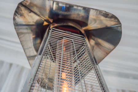Heating lamp heater placed among the tables of an open cafe 免版税图像 - 114999493