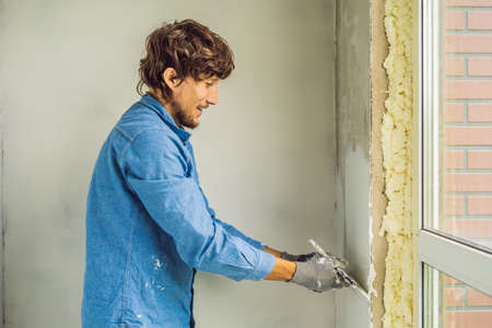 Master is applying white putty on a wall and smearing by putty knife in a room of renovating house in daytime Banque d'images - 114996995