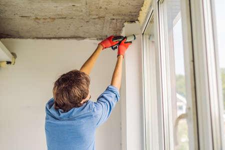 Man in a blue shirt does window installation Standard-Bild - 114902826