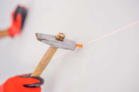 Man twists a screw into the wall Reklamní fotografie