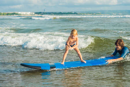 Father or instructor teaching his 4 year old son how to surf in the sea on vacation or holiday. Banque d'images