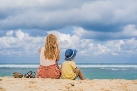 Mom and son travelers on amazing Melasti Beach with turquoise water, Bali Island Indonesia. Traveling with kids concept