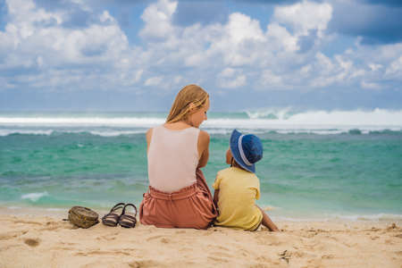 Mom and son travelers on amazing Melasti Beach with turquoise water, Bali Island Indonesia.