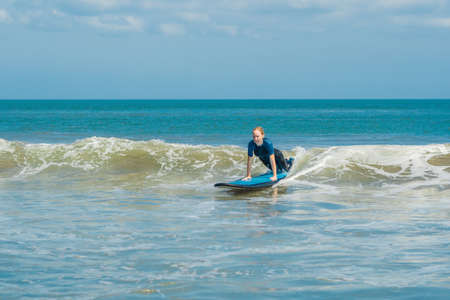 Joyful young woman beginner surfer with blue surf has fun on small sea waves. Stock fotó - 114898951