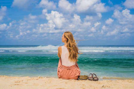Young woman traveler on amazing Melasti Beach with turquoise water, Bali Island Indonesia