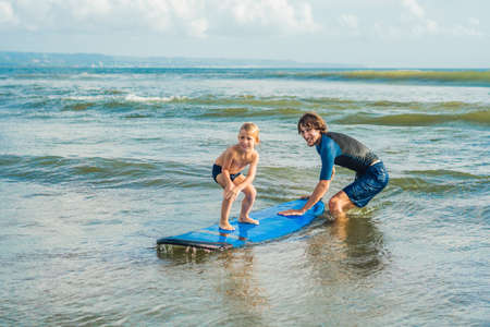 Father or instructor teaching his 4 year old son how to surf in the sea on vacation or holiday. Stockfoto