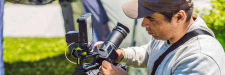 a professional cameraman prepares a camera and a tripod before shooting. BANNER, LONG FORMAT