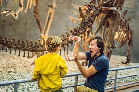 Dad and boy watching dinosaur skeleton in museum. Stock Photo