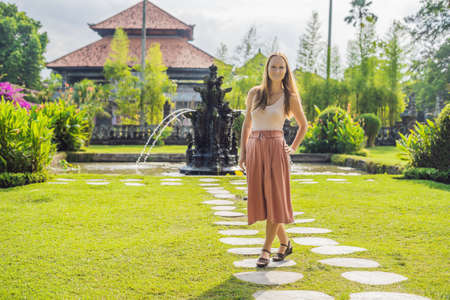 Young woman tourist in Traditional balinese hindu Temple Taman Ayun in Mengwi.