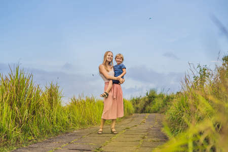 Mom and son tourists in Campuhan Ridge Walk , Scenic Green Valley in Ubud Bali. Traveling with children concept