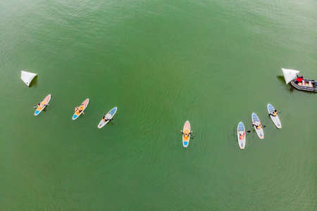 Strong men floating on a SUP boards in a beautiful bay on a sunny day. Banco de Imagens