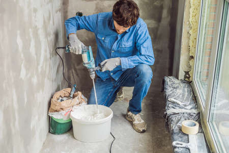Young male painter kneads putty with water in a bucket using a hand-held mixer for building mixes Imagens - 114590707