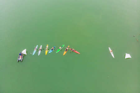 Strong men floating on a SUP boards in a beautiful bay on a sunny day. Stock Photo