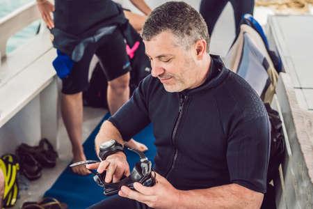 Diver prepares his equipment for diving in the sea Standard-Bild