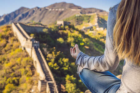 Happy cheerful joyful tourist woman at Great Wall of China meditates on vacation