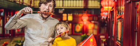 Enjoying vacation in China. Happy tourists dad and son with a Chinese flag