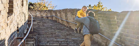 Happy cheerful joyful tourists dad and son at Great Wall of China having fun on travel