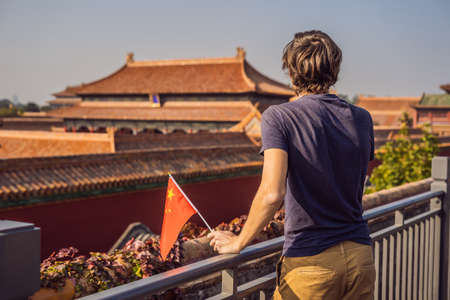 Enjoying vacation in China. Young man with national chinese flag in Forbidden City. Travel to China concept. Visa free transit 72 hours, 144 hours in China