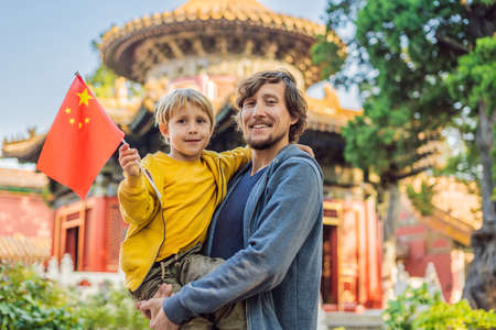 Enjoying vacation in China. Happy family with national chinese flag in Forbidden City. Travel to China with kids concept. Visa free transit 72 hours, 144 hours in China Stock Photo
