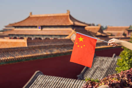 Enjoying vacation in China. Young woman with national chinese flag in Forbidden City. Travel to China concept. Visa free transit 72 hours, 144 hours in China