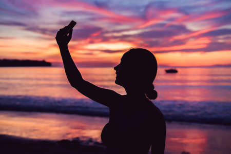 Young asia woman selfie with mobile phone on a beach at sunset in summer, Phuket, Thailand. Stock Photo