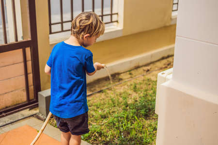 Cute little toddler boy watering plants with watering can in the garden. Adorable little child helping parents to grow vegetables and having fun. Activities with children outdoors
