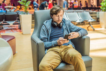 A man in the lounge area at the airport is waiting for his plane, uses a smartphone and headphones. Young smiling man with beard holding smartphone in hands working in airport while waiting for plane departure