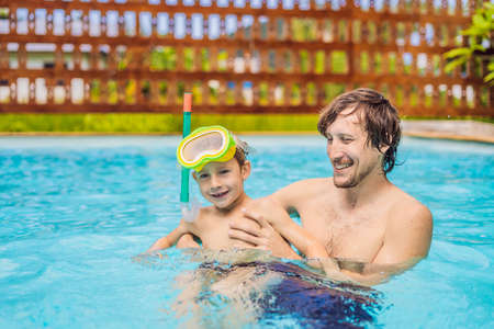 Dad and son in swimming Goggles have fun in the pool Stock Photo