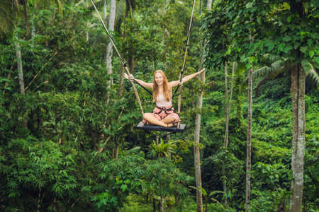 Young tourist woman on the swing in the jungle rainforest of a tropical Bali island