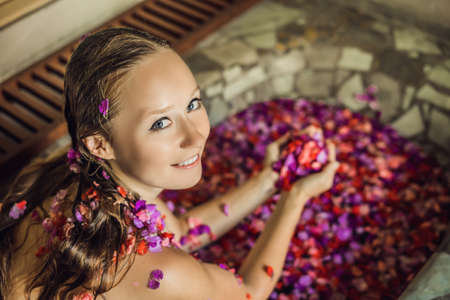 Attractive Young woman in bath with petals of tropical flowers and aroma oils. Spa treatments for skin rejuvenation. Alluring woman in Spa salon. Luxury spa and skin care Imagens