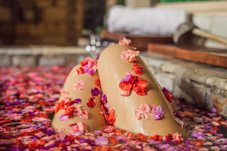 Attractive Young woman in bath with petals of tropical flowers and aroma oils. Spa treatments for skin rejuvenation. Alluring woman in Spa salon. Luxury spa and skin care Stockfoto