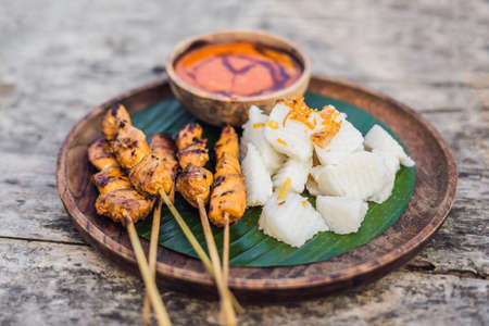 Indonesian chicken satay or Sate Ayam served with lontong, soy sauce and peanut sauce lifestyle food
