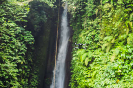 Little quadcopter flying around waterfall Leke Leke Bali island Indonesia.
