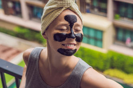 Beautiful young woman relaxing with face mask at home. Happy joyful woman applying black mask on face Stockfoto