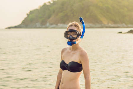 Beautiful woman with mask and flippers for snorkeling on the beach