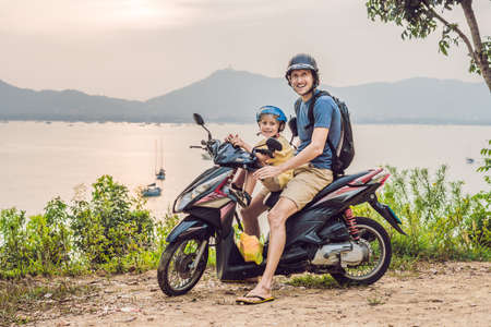 Dad and son on a moped against a sunset background 版權商用圖片