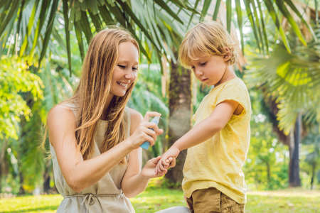 Mom and son use mosquito spray.Spraying insect repellent on skin outdoor Reklamní fotografie