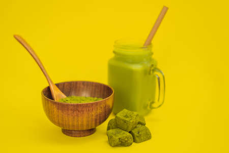 Green tea latte with ice in mason jar, matcha powder and candy made of matcha on yellow background. Homemade Matcha Stock Photo