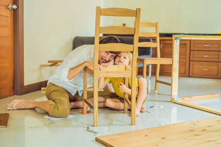 Father and son assembling furniture. Boy helping his dad at home. Happy Family concept
